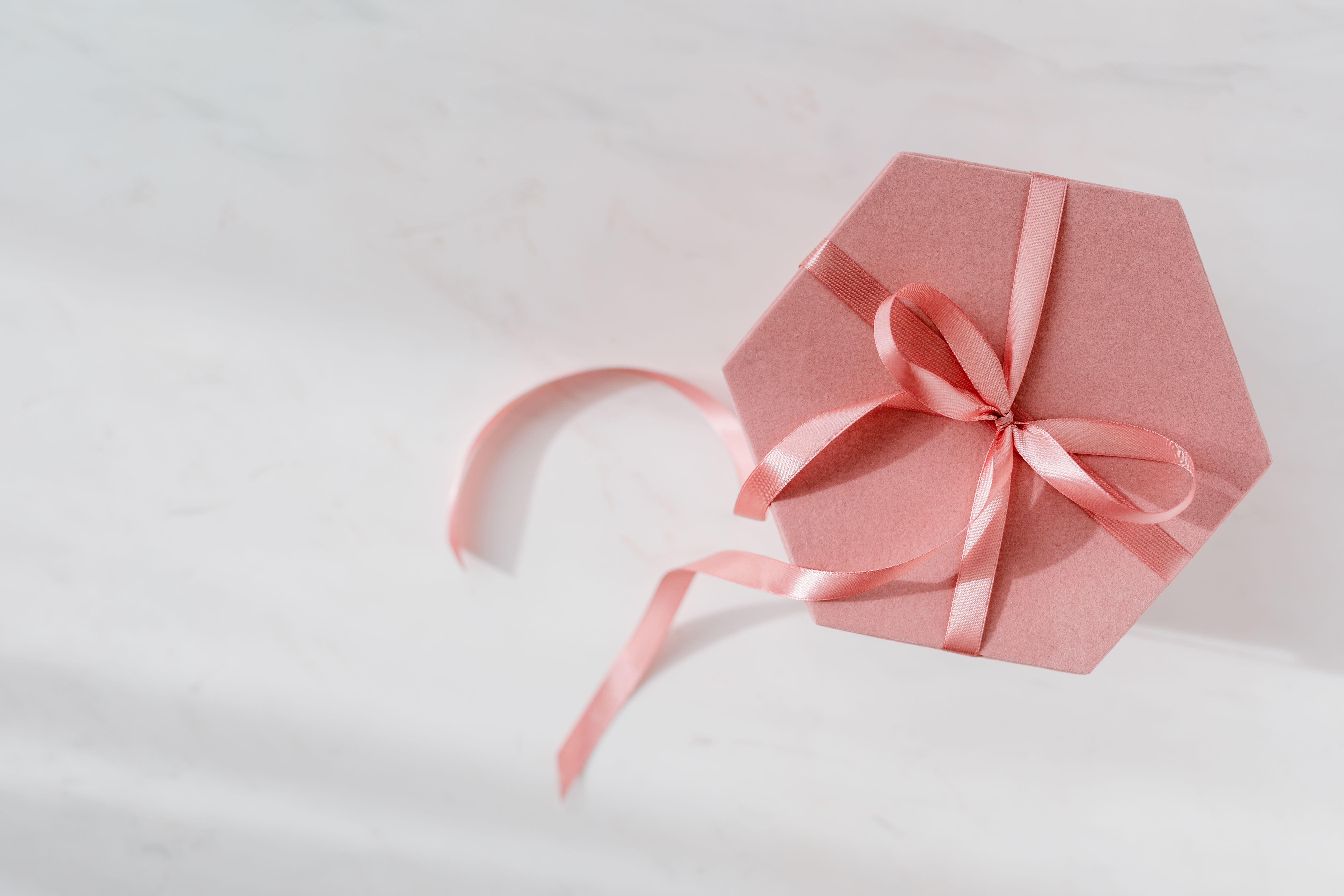 kaboompics_Light pink velvety box with satin ribbon on white marble